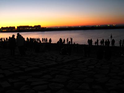 海辺で日の出を待つ人々